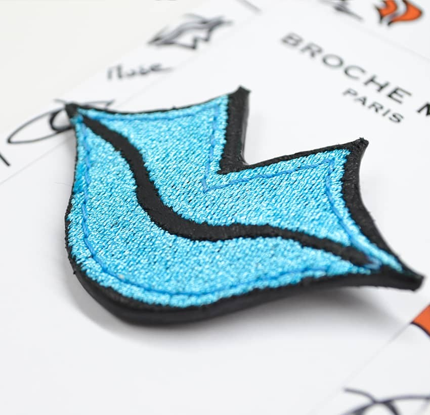 Woman's MUSE brooch embroidered in sky blue GLORIA BALENSI on calf leather, lying down view